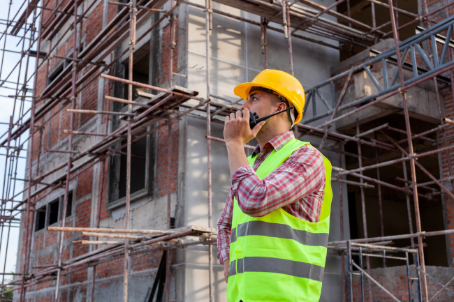 Construction workers in Louisville, KY can communicate to large groups by using two way radios vs. cell phones.